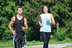 Fitness couple jogging in park. Young fitness couple of man and women jogging in park stock photo