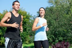 Fitness couple jogging in park. Young fitness couple of man and woman jogging in park royalty free stock photography