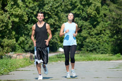 Fitness couple jogging in park Stock Images