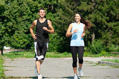 Fitness couple jogging in park. Young fitness couple of men and women jogging in park royalty free stock photography