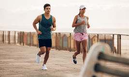 Fitness couple jogging on the sea side promenade Royalty Free Stock Photo