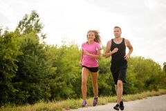 Fitness couple running together, full length portrait. Royalty Free Stock Image