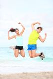 Fitness couple jumping fun. On beach during outdoor workout running. Fit young Asian women fitness model and Caucasian man stock photo