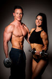 Fitness couple poses in studio - fit man and woman. Fitness couple poses in studio with dumbbells showing muscles - fit men and woman stock image