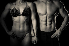 Fitness couple poses in studio - fit man and woman stock photo