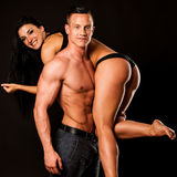 Fitness couple poses in studio - fit man and woman Stock Images