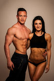 Fitness couple poses in studio - fit man and woman. Fitness couple poses in a studio - fit men and woman stock images
