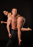 Fitness couple poses in studio - fit man and woman. Fitness couple poses in studio - fit men carry fit woman stock photo