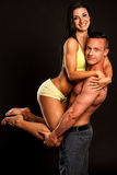 Fitness couple poses in studio - fit man and woman. Fitness couple poses in studio - fit men holding fit woman stock image