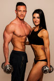 Fitness couple poses in studio - fit man and woman. Fitness couple poses in studio - fit men and women with dumbbells royalty free stock photos