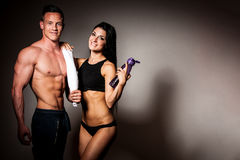 Fitness couple poses in studio - fit man and woman. Fitness couple poses in studio - fit men and women after workout with towel and bottle of water royalty free stock image
