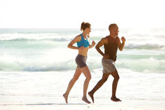 Fitness couple running along the sea on beach. Full length side  portrait of young fitness couple running along the sea on beach Stock Photos