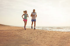 Fitness couple running on the beach. Happy fitness couple running on the beach Royalty Free Stock Images