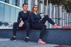 Fitness couple in a sportswear, sexy blonde girl and a handsome muscular guy sitting on a bench against a skyscraper. Young fitness couple in a sportswear, sexy Stock Images