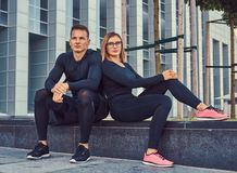 Fitness couple in a sportswear, sexy blonde girl and a handsome muscular guy sitting on a bench against a skyscraper. Young fitness couple in a sportswear, sexy Royalty Free Stock Image