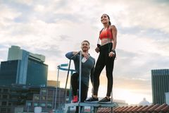 Fitness couple standing on rooftop of a building. Low angle view of a fitness men and women standing on metal stairs on terrace of a building. Fitness couple royalty free stock photo