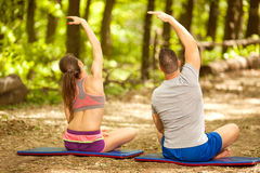 Fitness couple stretching outdoors in park. Fitness, sport, friendship and lifestyle concept - smiling couple execirse in green forest Stock Photo