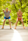 Fitness couple stretching outdoors in park. Fitness, sport, friendship and lifestyle concept - smiling couple execirse in green forest Royalty Free Stock Photography