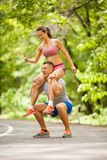 Fitness couple stretching outdoors in park Royalty Free Stock Image