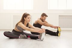 Fitness couple at stretching training indoors. Fitness couple at legs stretching training, making aerobics exercise at gym, copy space royalty free stock photo
