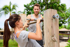 Fitness couple training on chin-up bar together. Woman helped by friend or private instructor on coaching session supervising exercises on outdoor beach gym Stock Photo