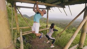 Fitness couple training sport exercise together on outdoor ground on natural landscape. Man doing pull up exercise stock footage