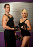 Fitness couple trains in gym with dumbbells Stock Images