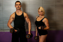 Fitness couple trains in gym with dumbbells Stock Photos