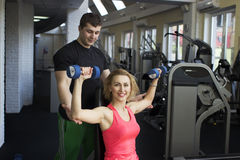 Fitness couple working out with dumbbells in gym Royalty Free Stock Photos
