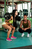 Fitness couple workout - fit man and woman train in gym Royalty Free Stock Photography