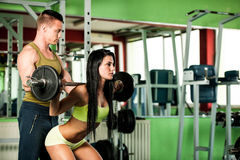Fitness couple workout - fit mann and woman train in gym Royalty Free Stock Photography