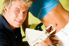 Fitness craze: trainer or coach measuring the body. Fat of a woman with a device stock photo