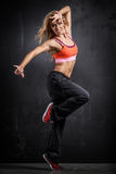 Fitness dancer. Girl in passionate pose on gray background Stock Images