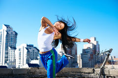 Fitness dancing girl on the roof blue sky. Young woman doing fitness urban Royalty Free Stock Photo