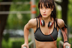 Fitness dark-haired young woman with headphones working out Royalty Free Stock Image