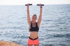 Fitness de treinenspieren van het Sportenmeisje met domoren Stock Foto