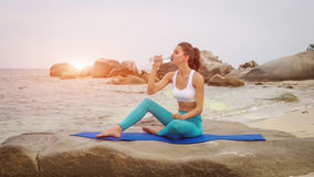 Fitness de vrouw drinkt water na het doen van sportoefeningen op strand bij zonsondergang stock fotografie