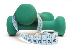 Fitness and diet. Close-up of green dumbbells and tape-line at the white background Royalty Free Stock Photography