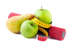 Fitness and Diet. Concept, green apples and pear with measuring tape and dumbbell Stock Images