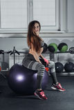 Fitness and diet concept - smiling sexy girl exercising with fitness ball at gym. Stock Image