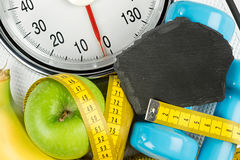 Fitness diet motivation concept. Fitness diet motivation background concept apple banana measuring tape and empty slate on white bathroom scale Royalty Free Stock Photo