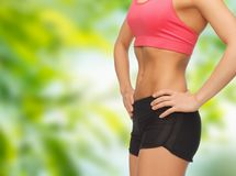 Close up of female torso and abdomen. Fitness, diet and slimming concept - close up of female torso and abdomen over green natural background Stock Photo