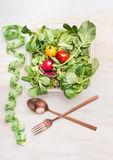 Fitness dieting salad with cutlery and measuring tape on white wooden background, top view. Mixed greens salad bowl stock photo