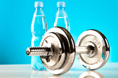 Fitness dumbbell. And soda bottles on the blue background Royalty Free Stock Image
