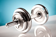 Fitness dumbbell. On the blue background Stock Images