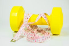 Fitness dumbbell and measuring tape Royalty Free Stock Photography