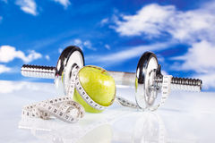Fitness dumbbells and apple Stock Photos
