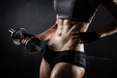 Fitness with dumbbells. Brutal athletic woman pumping up muscles with dumbbells Stock Images