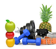 Fitness dumbbells with pineapple and apples Stock Image