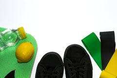 Fitness elastic gum expanders, green karemat, black sneakers, bottle with water and lemon on white background. Sport flat lay royalty free stock photos
